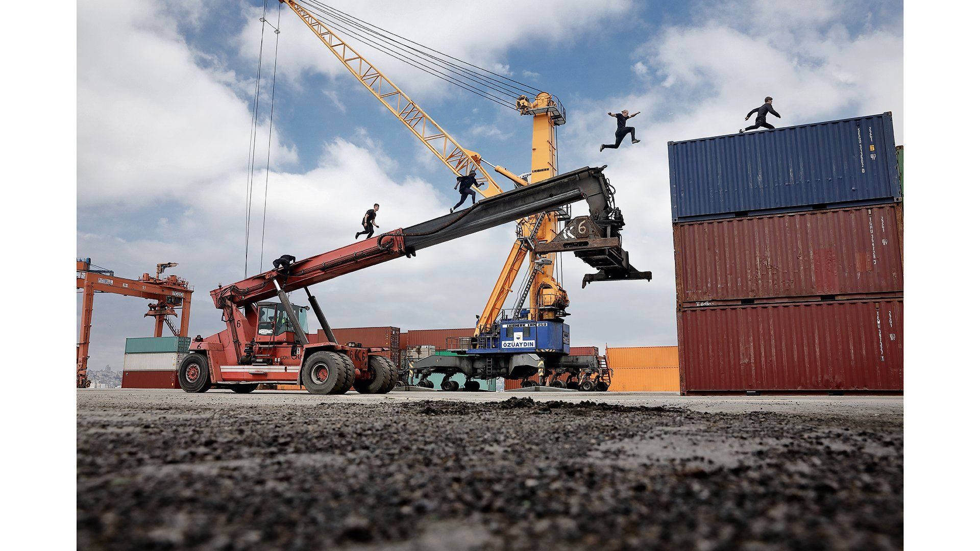 4 men running up a crane on to shipping containers